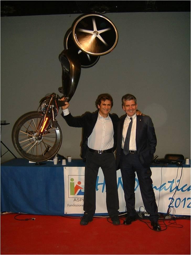 Alex Zanardi, con l'handbike in mano, accanto a Andrea Pontremoli