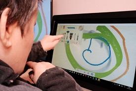 una ragazza disabile disegna su no schermo touch